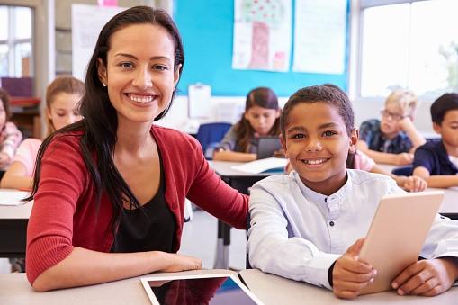 Portrait of teacher with elementary school teacher at his desk