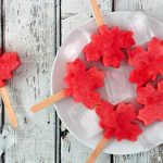 Canadian maple leaf watermelon pops on a plate against rustic white wood