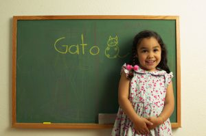 Girl standing by chalkboard with GATO on it