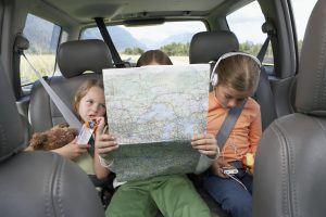 two children who are english learners backseat reading a map