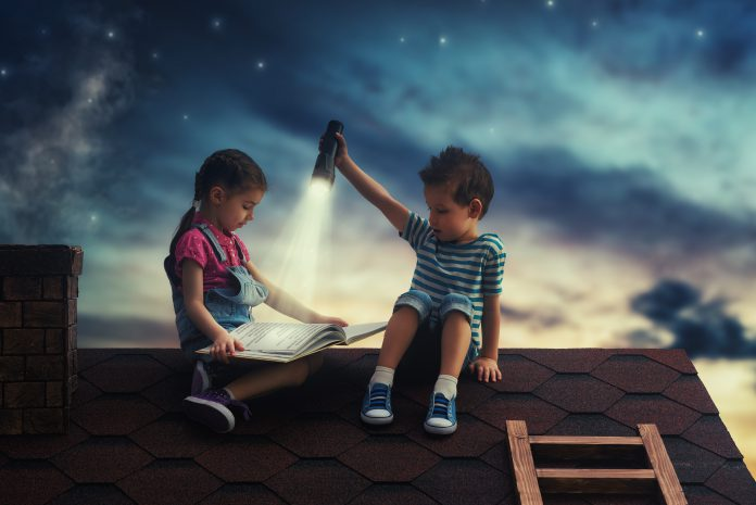 Children reading a book sitting on the roof of the house. Boy and girl reading by the light of a flashlight at night.