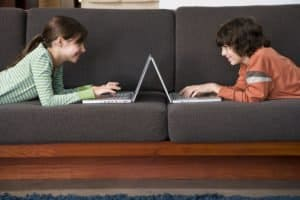 Preteen boy and girl using laptop computers