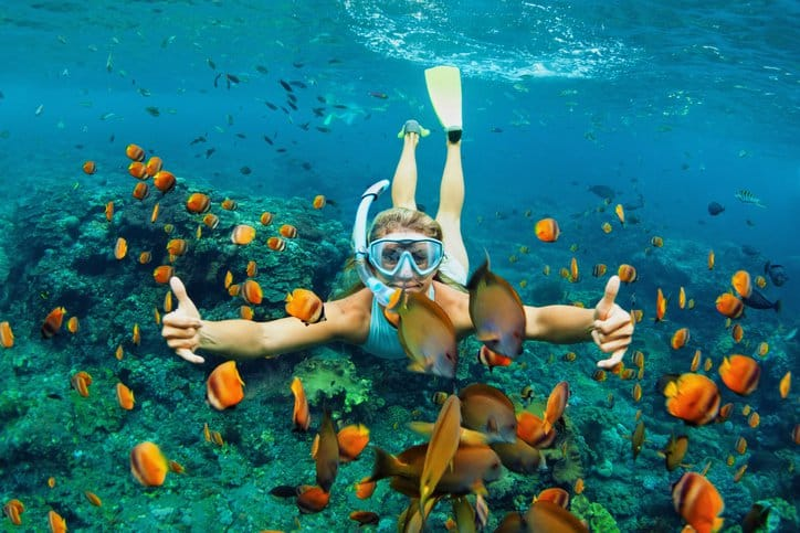 girl in snorkeling mask dive underwater with tropical fishes in coral reef sea pool in Hawai'i.