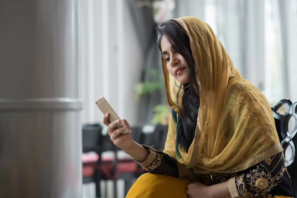 Indian woman in yellow headscarf looking at mobile phone.