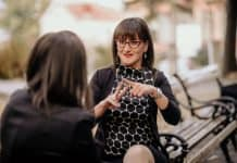 woman in black dress and glasses performing sign language to another woman on a bench