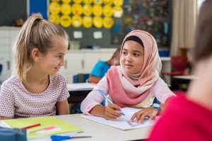 Muslim girl and Caucasian girl communicating by smiling at each other.