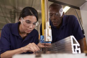 A mature, Black carpenter Training Female Asian-American Apprentice To Use Mechanized Saw