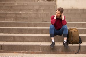 A young woman sits alone on the steps.