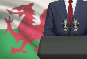 Welsh flag with suited figure in front of microphones.