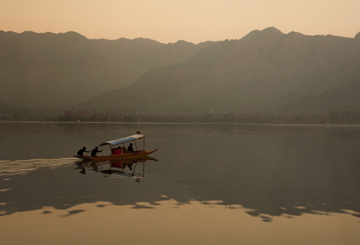 A boat glides across the serene Dal Lake in Kashmir