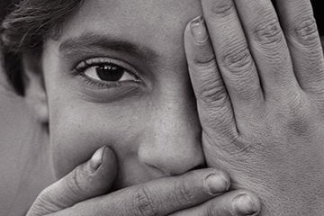 Black & white photo of Syrian girl showing one eye, closing mouth.