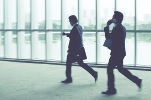 Businesspeople on the phone, rushing through an airport