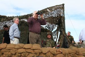 Rep. Price looking through binoculars at a military post.