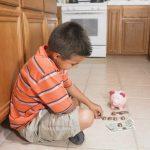 Boy counting money on floor
