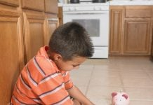 Boy counting money on floor