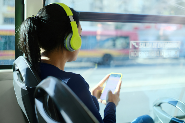 Woman With Headphones Listening To Music While Commuting To Work Using Public Transportation