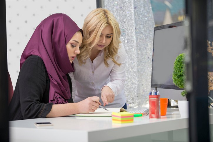 European woman and asian muslim woman working together on same project.