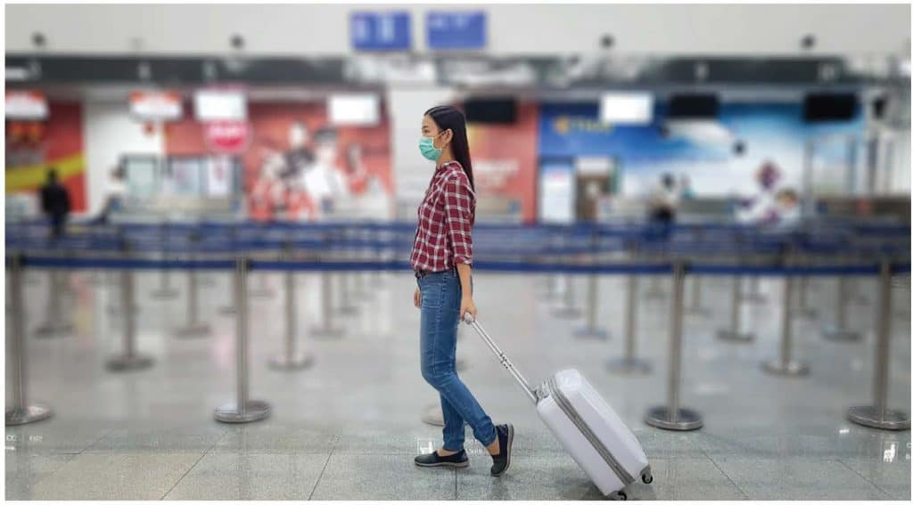 Girl wearing a mask drags her suitcase through a deserted airport