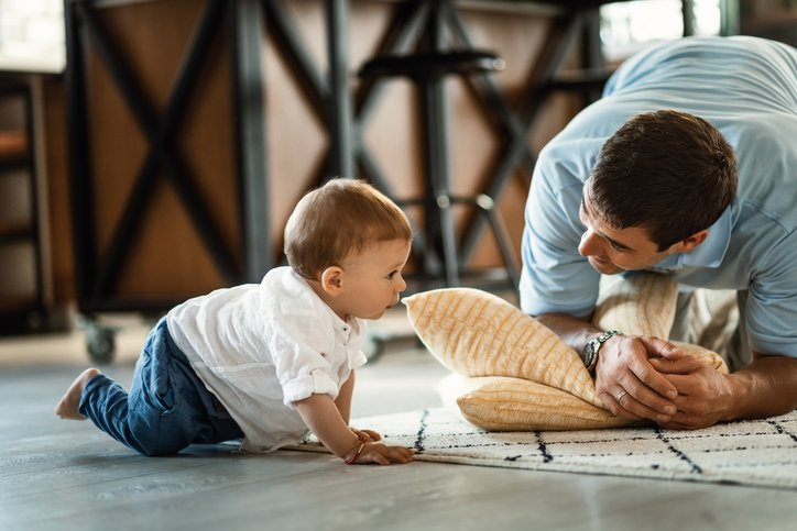 Happy father talking to his small son who is crawling on the floor in the living room.