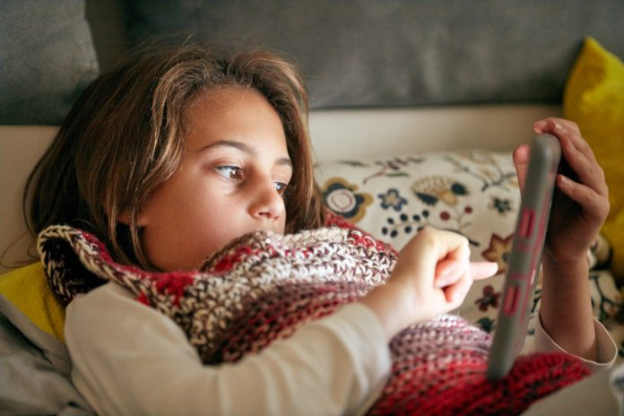 Little girl studying and doing homework at home with tablet.