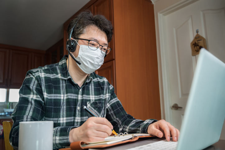 An Asian man studying on his laptop wearing a medical mask