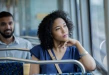 Serious young woman gazes out train car window while using public transportation to reach her destination. Young commuters are riding train.