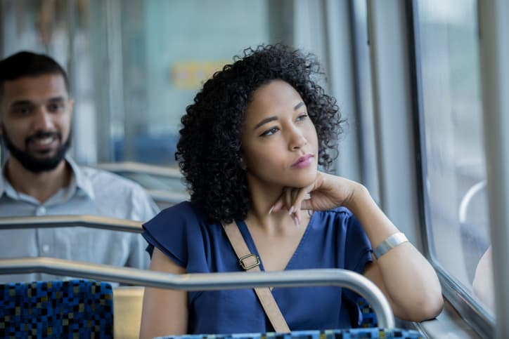Serious young woman gazes out train car window while using public transportation to reach her destination.