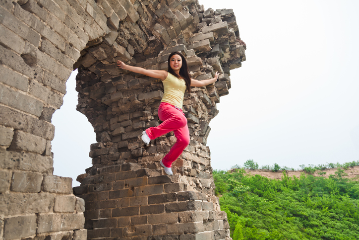 East Asian girl jumping through the Great Wall of China