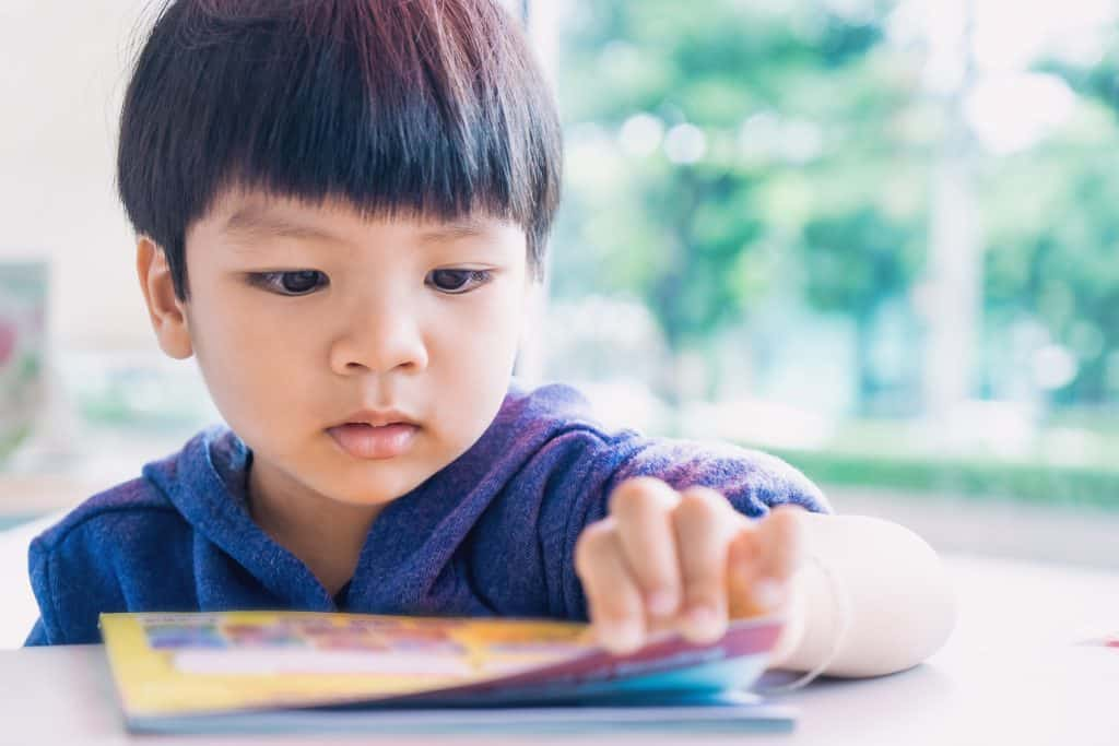 Young Asian-American boy reading a educational play book.
