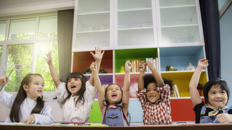 Group of multi-ethnic little kids raising their hands in happiness in a classroom