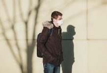 Male student with backpack and mask standing out in the cold.