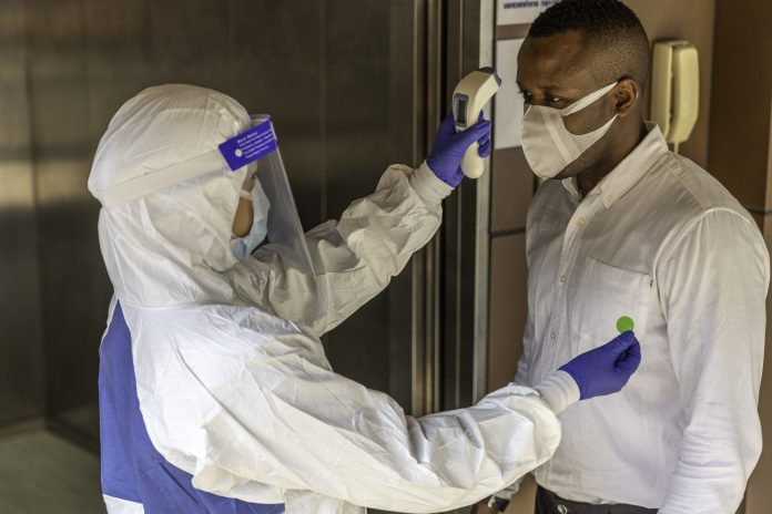 Nurse in PPE suit uses infrared thermometer measuring temperature with African male worker scanning for Coronavirus or Covid-19 symptom at office elevator International medical healthcare system