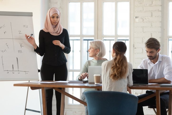 millennial female Arabic speaker explaining presentation to older and young colleagues at office.