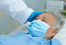 Doctor checking Asian senior patient wearing a face mask in hospital for protection from infection