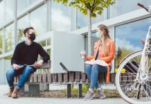 Students on university campus keeping social distance and wearing face masks due to coronavirus