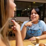 Two young women drinking coffee, talking in sign language. Deaf friends or couple communicating, having fun, pleasant conversation, sitting together