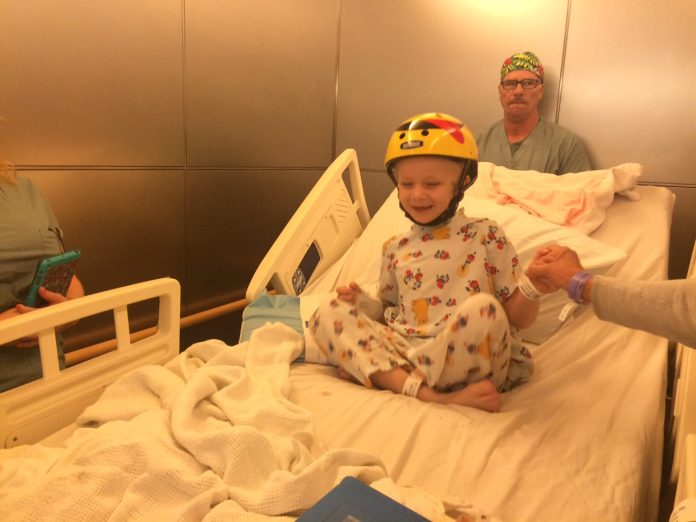A young boy smiling in a hospitla bed, wearing a protective helmet after brain surgery.