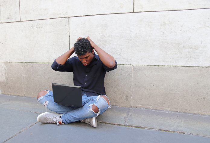 Frustrated young man using laptop