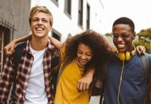 Close up of three college friends standing in the street with arms around each other. Cheerful boys and a girl wearing college bags having fun walking outdoors.