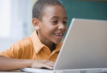 Happy African-American boy working on laptop