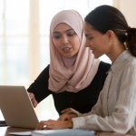Focused muslim female mentor teacher teaching intern worker learning new skills