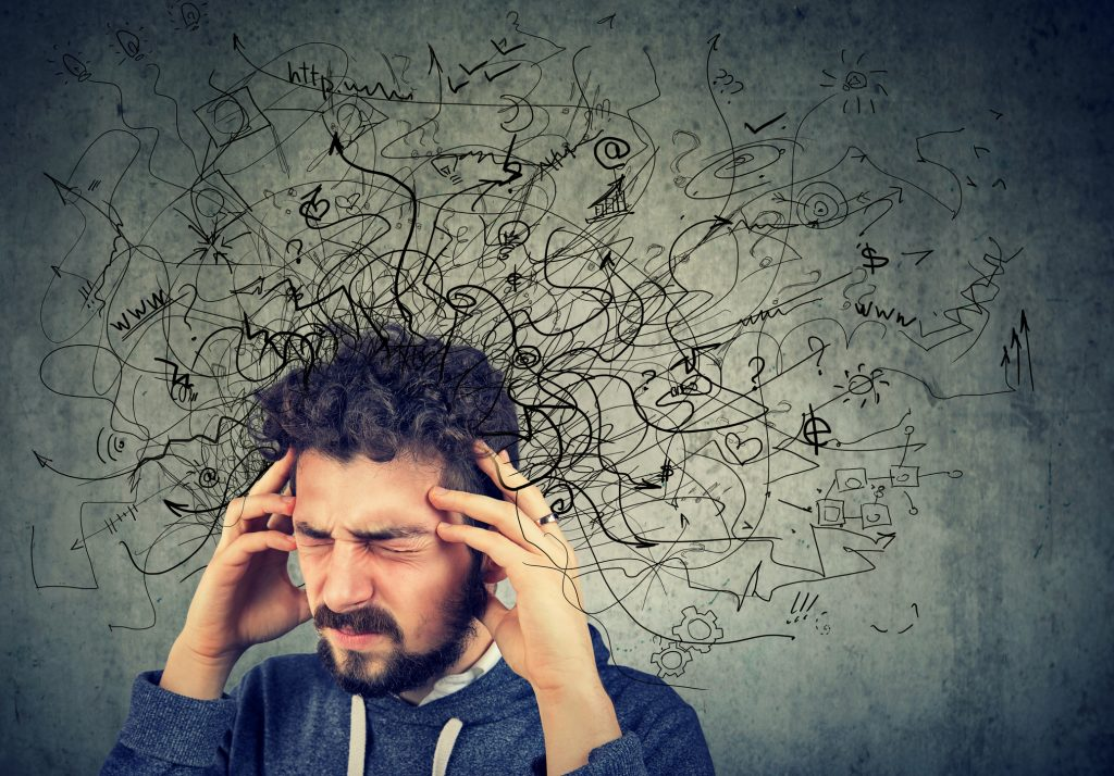 Pained, stressed young man with a tangled thoughts coming out of his head