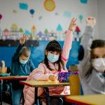 Kids in class with masks, raising their hands.