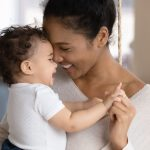 Smiling young African American mother hugging little infant