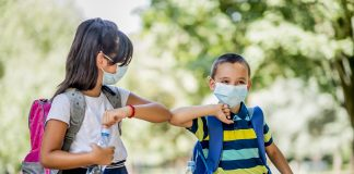 Two school children using elbow bump as an alternative handshake outdoors