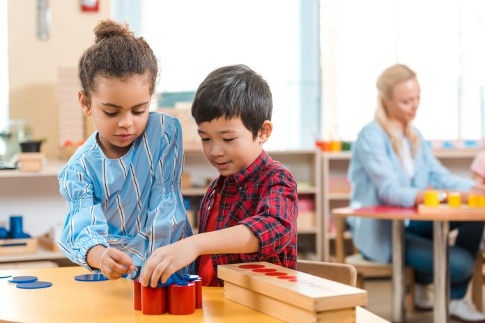 kids folding educational game with teacher at background in montessori class