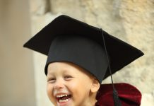 little boy dressed as a graduate with a book