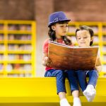Two young kids sitting on a bright yellow platform reading a big storybook together