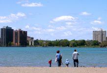 Family looks across lake at Detroit shyline