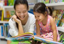 Parent and child reading books together in the library.
